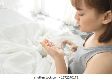 Young beautiful asian woman with short hair,wore gray clothes in white bed at home, She had fever, sickness, discomfort, taking medicine.