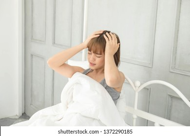 Young beautiful asian woman with short hair,wore gray clothes in white bed at home, She pain in the head,headache