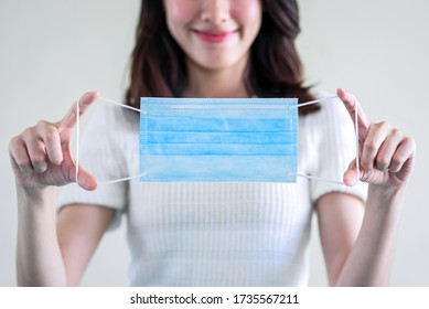 young  beautiful asian woman showing how to wear a medical mask or  showing how to correctly wear hygiene surgical mask step by step on white background