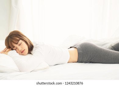 Young beautiful asian woman sleeping,lying on white bed ,  close one's eyes in the morning,soft and selective focus
