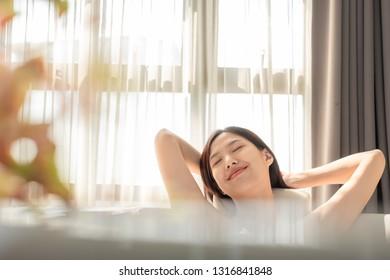 Young beautiful Asian woman taking bath in  bathtub, massaging perfect skincare