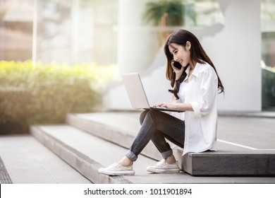 Young and beautiful Asian woman talking on mobile phone and working with her laptop while sitting on the steps outside the modern office building in the urban city