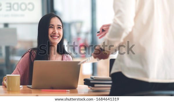 Young beautiful asian woman talking and discussing with her friend while working with laptop in modern office.