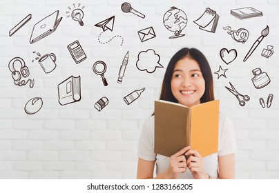 Young beautiful Asian woman thinking gesture and holding book on white brick wall background with freehand doodle school supplies, stationery graphic.Concept of education and learning.
