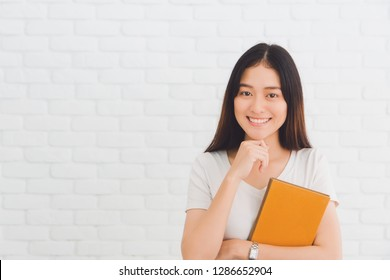 Young beautiful Asian woman thinking gesture and holding book on white brick wall background.Concept of education and learning.