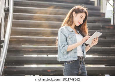 Young and beautiful Asian woman using her tablet PC while sitting on the steps outside the modern office building in the urban city