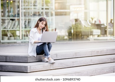 Young and beautiful Asian woman using her laptop PC while sitting on the steps outside the modern office building in the urban city