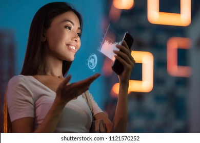 A young beautiful asian woman using innovative technologies as an application in her smart phone to monitor sales analytics. Communicate about business, future, technology, statistics, data, people