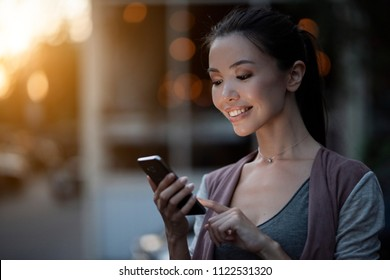 A young beautiful asian woman using an application in her smart phone to read email, send text message, chat, browse or shop online. Communicate about people, phone, technology, applications