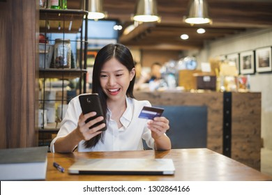Young beautiful asian woman using smart phone and credit card for shopping online in coffee shop cafe