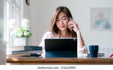 Junge schöne asiatische Frau mit Smartphone und mit Laptop arbeiten, während sie am Büroschreibtisch sitzt, von zu Hause aus arbeitet.