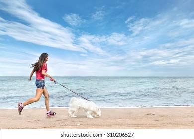 Young beautiful asian woman walking with dog near sea
