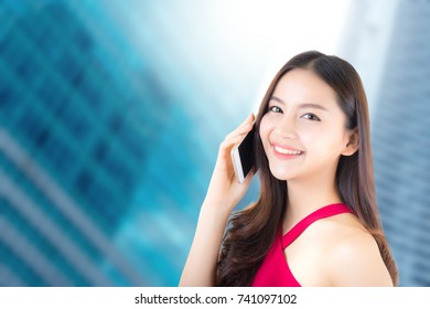 Young beautiful asian woman wear red dress talking on smart phone with happy and success on city background - communication business concept.
