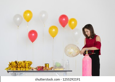 young beautiful Asian woman wearing red blouse and black pants inflating colorful balloons with helium gas tank, wrapping gifts with golden paper, decoration goods line-up on table, prepare for party,