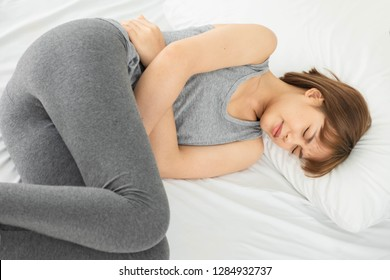 young beautiful asian woman wearing  gray clothes,Wake up in a white bed in the morning, The body aches, Hug hands on the stomach Curled up with abdominal pain, stomachache