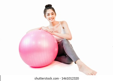 Young beautiful asian woman wearing a white tank top Exercise with pink yoga ball isolated on white background