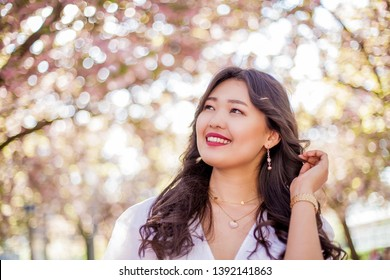 A young beautiful Asian woman in a white dress walks in a flowered park. Sakura. Blooming trees. Spring.