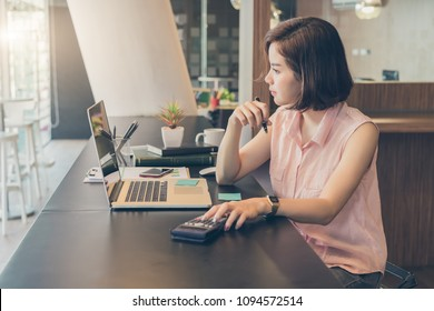 Young beautiful asian woman working about financial with laptop and calculator.financial and accounting concept.