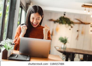 Young beautiful Asian woman working in coffee shop cafe, using computer laptop about business work and online shopping, smile and happy.