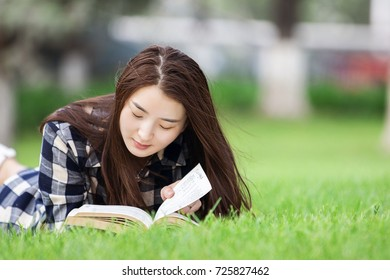 Young, beautiful Asian women sit on the grass reading