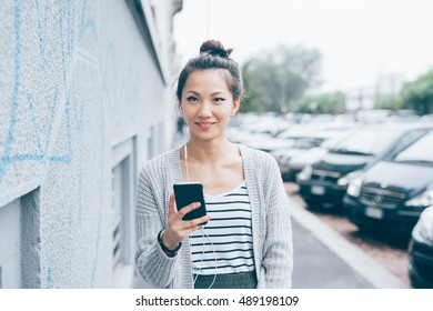young beautiful asiatic woman holding a smart phone listening music with earphones, looking at camera smiling - technology, social network, communication concept