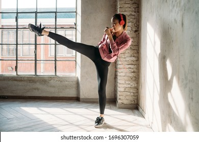 Young beautiful asiatic woman indoors at home training boxing listening music - healthy, sportive, wellbeing concept