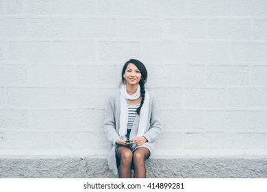 Young beautiful asiatic woman sitting leaning against a white wall, listening music with earphones and smart phone hand hold, looking in camera, smiling - technology, music, happiness concept