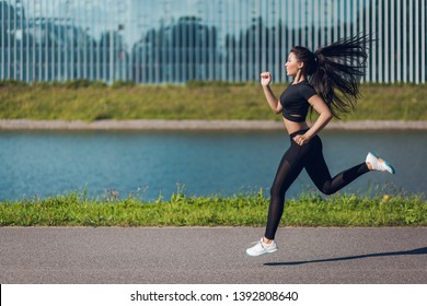 Young beautiful athlete girl in black training kit runnning along a river