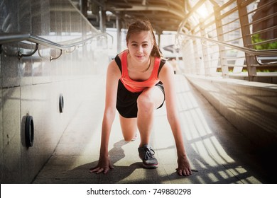 Young beautiful athlete on a race track is ready to run, preparing to start jogging.
