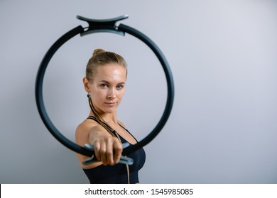 Young, beautiful, athletic girl is doing exercises with the Pilates ring in the gym on a gray background. Sporting Slavic girl in a blue, green suit. Copy space, gray background, sport banner for