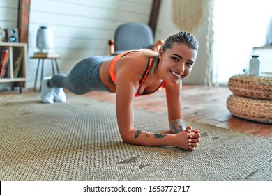 Young beautiful athletic girl in leggings and top makes an exercise plank. Healthy lifestyle. A woman goes in for sports at home.