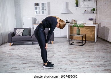 Young beautiful athletic girl in leggings and a top does stretching exercises. Healthy lifestyle. The woman goes in for sports at home.