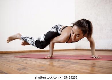 Young beautiful athletic girl practicing indoor yoga arm-balance. Eka Pada Koundiyanasana