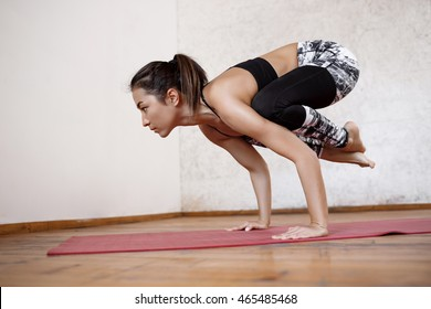 Young beautiful athletic girl practicing indoor yoga arm-balance handstand Crane Crow Pose, Bakasana with arms straight