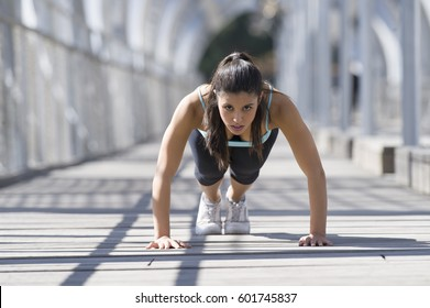 young beautiful and athletic sport woman doing push up before running in urban training workout on modern metal city bridge in female runner body care concept