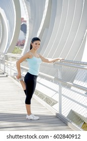 young beautiful and athletic sport woman stretching leg muscles before running and jogging in urban training workout leaning on modern metal city bridge in female runner body care concept
