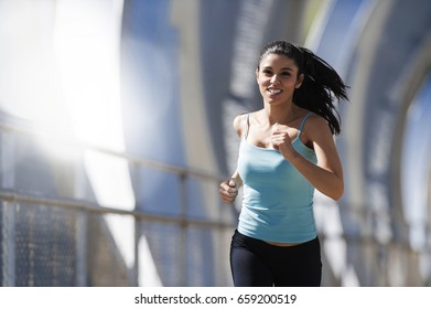 young beautiful and athletic sport woman running and jogging in urban training workout crossing modern metal city bridge in female runner body care and healthy lifestyle concept with lens flare