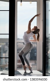 Young beautiful athletic woman blonde in white sportswear doing yoga and stretching on the balcony at home. Stands on the fingers and performs dance steps. Concept of home sport and active lifestyle.