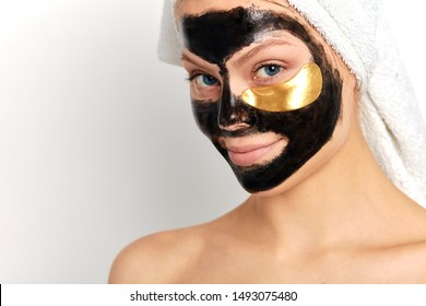 Young beautiful attarctive smiling woman with a mask for the face of the therapeutic black mud. close up portrait, beauty, wellness, wellbeing, health care , isolated white background.