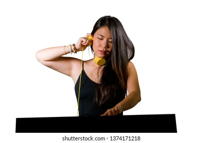 young beautiful and attractive Asian Chinese DJ woman remixing music at night club wearing headphones in clubbing party and deejay  lifestyle concept isolated on white background