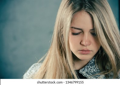 The young beautiful attractive blond girl in school uniform has bowed her head. She is crying. The woman is sad. Emotional portrait frustrated blond girl
