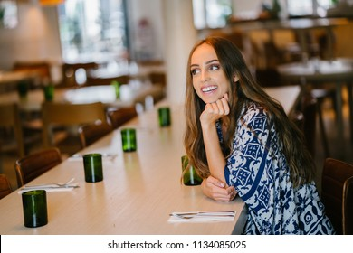 A young, beautiful, attractive and fashionably dressed brunette Caucasian woman with blue eyes is sitting in a cafe and enjoying the morning. She is wearing a blue and white scarf.
