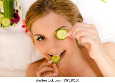 Young beautiful attractive girl blond woman lying with slices of cucumber on eyes and happy smiling