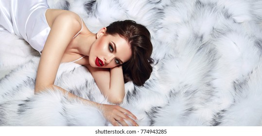 Young beautiful attractive girl in a white silk dress lies on a white fluffy fur.Fashion, beauty, shakarnaya, glamor, luxurious, make-up, hairstyle.Fashion, beauty, make-up, cosmetics, hairstyle.