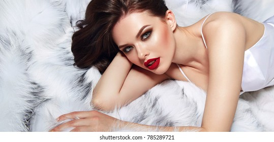 Young beautiful attractive girl in a white silk dress lies on a white fluffy fur.