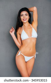 Young and beautiful. Attractive young smiling woman in white bikini posing against grey background