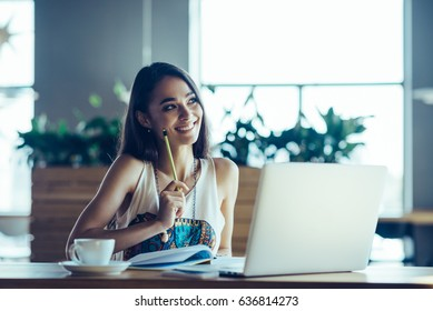 Young beautiful attractive woman, head hunter searching for new colleagues at her workplace in an office. Modern ux/ui designer making mobile application on her notebook during working day.