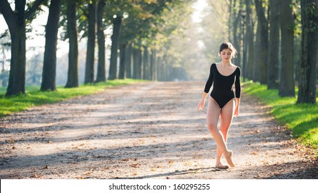 Young beautiful ballerina dancing outdoors in a parkway with trees. Ferrara, Italy. Ballerina Project.
