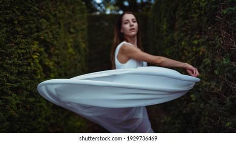 Junge schöne Ballerina tanzt im Freien mit weißem, langes Kleid in einem Park. Ballerina-Projekt. Konzentriere dich auf den Schleier.