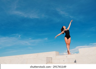 Young beautiful ballerina dancing outdoors in a modern environment with blue cloudy sky background. Ballerina Project. Filtered image.
